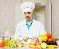 Cocinero de sexo masculino que cocina lechuga Fotos de archivo libres de regalías