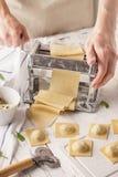 Cocinero de sexo masculino que hace los raviolis con la máquina de las pastas fotos de archivo libres de regalías