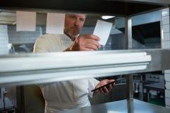 Cocinero de sexo masculino que lee una orden Fotos de archivo