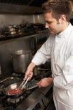 Cocinero de sexo masculino que prepara la comida en la cocina en restaurante imágenes de archivo libres de regalías