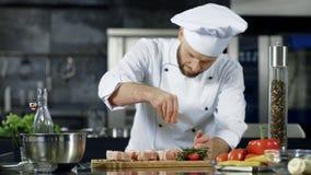 Cocinero de sexo masculino que sala la carne en la c?mara lenta en la cocina Hombre profesional que cocina el plato almacen de video