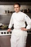 Cocinero de sexo masculino que se coloca al lado de la cocina fotos de archivo