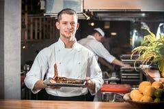 Cocinero de sexo masculino que sostiene el plato Imagenes de archivo