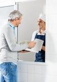 Cocinero de sexo masculino Selling Pasta Packets a servir fotografía de archivo