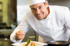 Cocinero de sexo masculino sonriente que adorna la comida en cocina Foto de archivo