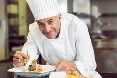 Cocinero de sexo masculino sonriente que adorna la comida en cocina foto de archivo libre de regalías