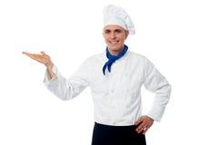 Cocinero de sexo masculino sonriente que muestra algo imagenes de archivo