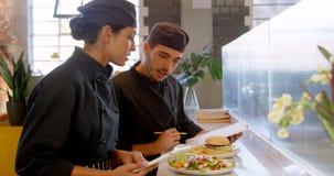 Cocinero de sexo masculino y de sexo femenino que obra recíprocamente con uno a 4k metrajes