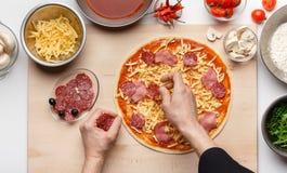 Cocinero Decorating Italian Pizza con el salami y el jam?n imagen de archivo libre de regalías