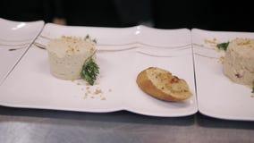 Cocinero Decorating Rabbit Pate con el Baguette tostado en una placa blanca almacen de metraje de vídeo