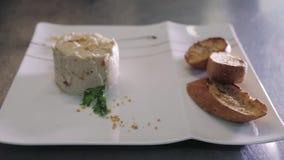 Cocinero Decorating Rabbit Pate con el Baguette tostado en una placa blanca metrajes