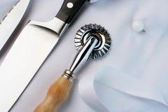 Cocinero del aprendiz; cuchillos, cortador de los pasteles, uniforme, visión angulosa Imagenes de archivo