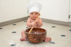 Cocinero del bebé con los ojos azules que revuelven adentro el cuenco con la cuchara de madera Fotos de archivo libres de regalías