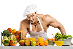 Cocinero del culturista del hombre, cocinando el jugo y el vegetab recientemente exprimidos Foto de archivo