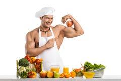 Cocinero del culturista del hombre con la manzana en bíceps Imagen de archivo