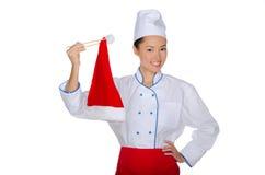 Cocinero del este que sostiene el sombrero de Papá Noel de los palillos Foto de archivo