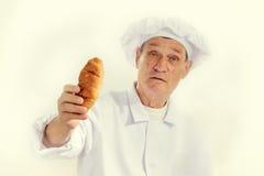 Cocinero del hombre con un cruasán Fotos de archivo