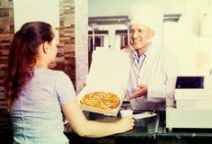 Cocinero del hombre que sostiene la pizza Imagen de archivo libre de regalías