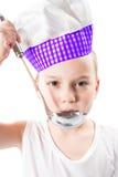 Cocinero del muchacho del niño que lleva un sombrero del cocinero con la cacerola aislada en el fondo blanco. Imagen de archivo libre de regalías
