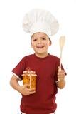 Cocinero del niño pequeño con un tarro de fruta conservada Fotografía de archivo libre de regalías