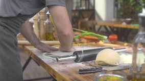 Cocinero del cocinero que asperja la harina en la pasta de la pizza mientras que rueda con el perno de rodillo Hombre que hace la almacen de video