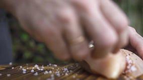 Cocinero del cocinero que pone el prendedero crudo del pollo en la tabla de madera Mano del cocinero que prepara la carne fresca  almacen de video