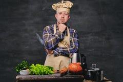 Cocinero del cocinero que presenta cerca de la tabla con muchas verduras frescas Fotografía de archivo