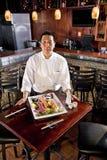 Cocinero del restaurante japonés que presenta el disco del sushi Imagenes de archivo