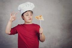 Cocinero divertido del niño con la pizza de la rebanada fotografía de archivo libre de regalías