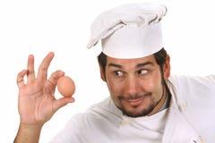 Cocinero divertido joven con el huevo Fotos de archivo libres de regalías