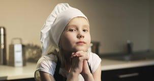 Cocinero dulce de la muchacha en un delantal y un casquillo blanco que se colocan en la cocina almacen de metraje de vídeo