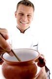 Cocinero elegante que cocina en crisol de la porcelana Fotografía de archivo libre de regalías