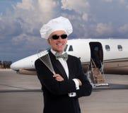 Cocinero elegante que presenta delante de un jet privado Fotografía de archivo