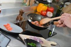 Cocinero en cocina del restaurante en la estufa Imagen de archivo libre de regalías