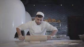 Cocinero en el uniforme blanco que trabaja lanzar rápido encima de la pasta y la rueda de ella con el rodillo de madera grande en metrajes