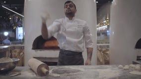 Cocinero en el uniforme blanco que trabaja lanzar rápido encima de la pasta y la rueda de ella con el rodillo de madera grande en almacen de video