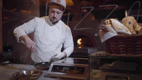 Cocinero en el uniforme blanco y el guante de goma que ponen los mejillones en la cacerola de aluminio con las manijas usando las almacen de video