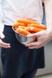 Cocinero en el uniforme que prepara los bastones frescos de la zanahoria Fotos de archivo libres de regalías