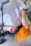 Cocinero en el uniforme que prepara los bastones frescos de la zanahoria Imagenes de archivo