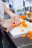 Cocinero en el uniforme que prepara los bastones frescos de la zanahoria Foto de archivo libre de regalías