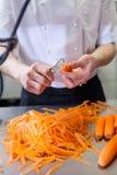 Cocinero en el uniforme que prepara los bastones frescos de la zanahoria Imagen de archivo libre de regalías