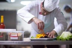 Cocinero en la cocina del hotel que prepara y que adorna la comida Foto de archivo libre de regalías