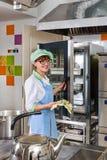 Cocinero en la cocina equipada Imagenes de archivo