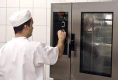 Cocinero en la estufa comercial Imagenes de archivo