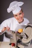 Cocinero en la máquina de cortar del alimento Imágenes de archivo libres de regalías
