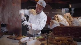 Cocinero en los guantes de goma blancos que asperja pescados con las especias sal y pimienta y que vierte con aceite de oliva Pre almacen de metraje de vídeo