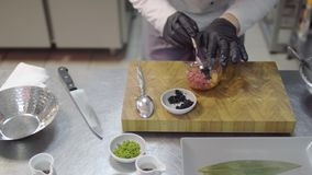 Cocinero en los guantes de goma negros que preparan el plato con el atún y los salmones crudos en primer moderno de la cocina del metrajes