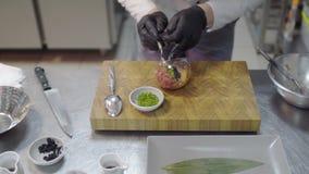 Cocinero en los guantes de goma negros que preparan el plato con el atún y los salmones crudos en primer moderno de la cocina del almacen de video