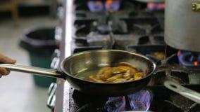 Cocinero en una cocina que cocina estilo del flambe almacen de video