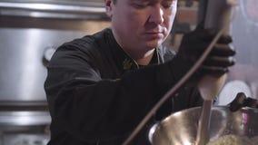 Cocinero en uniforme y guantes de goma negros del cocinero que azota el sause con la licuadora en cierre de aluminio grande del c almacen de video
